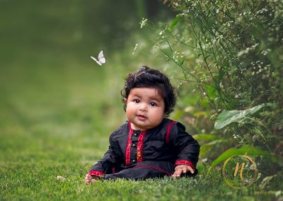6 months old boy sitting in grass with butterfly