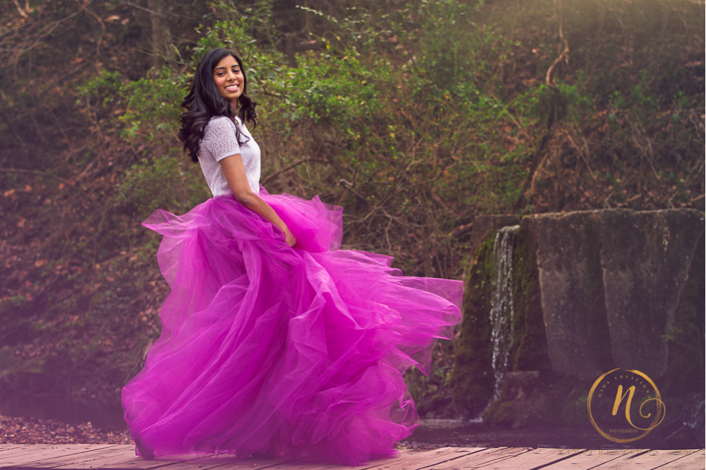 high school senior girl in a purple tulle skirt, dancing with a waterfall.