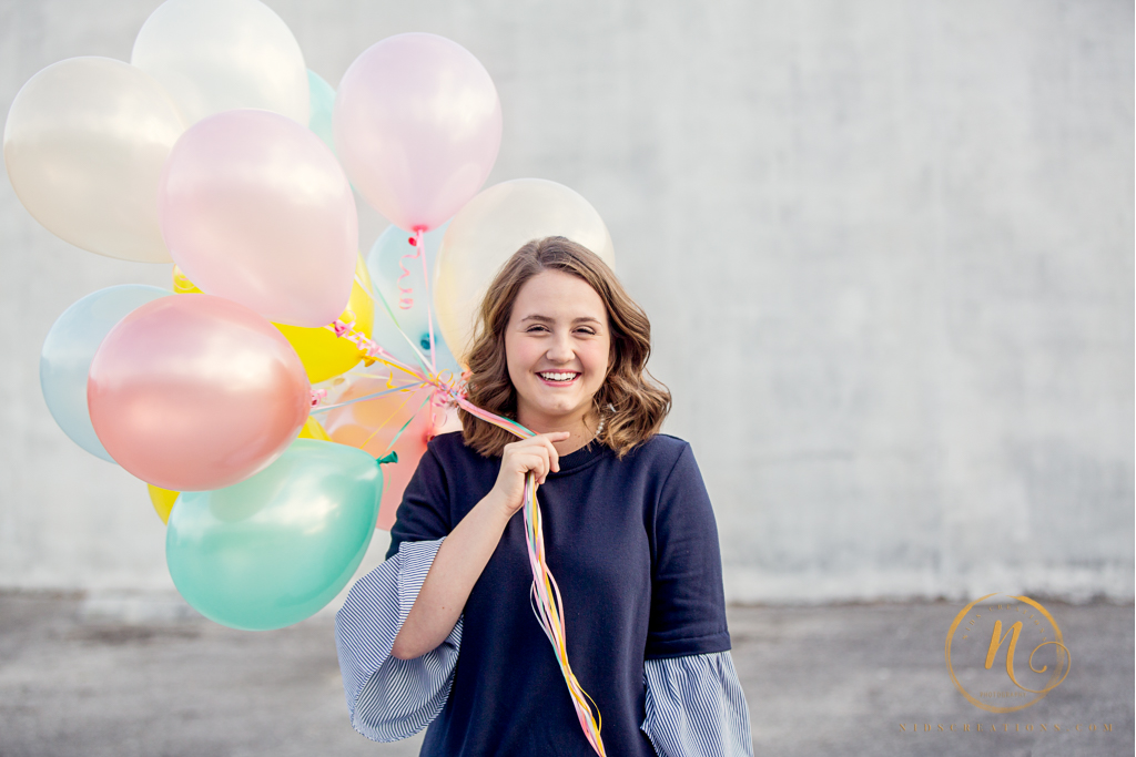 High school senior girl holding pastel color balloons