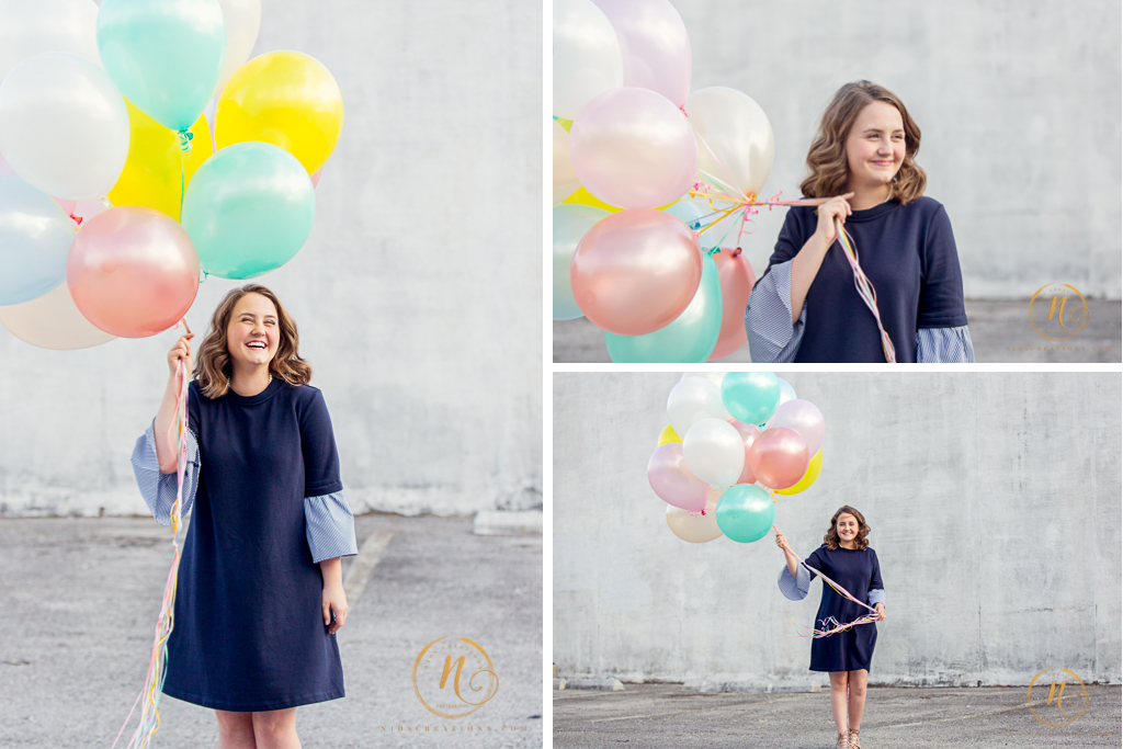 High school senior girl in navy blue dress holding pastel color balloons